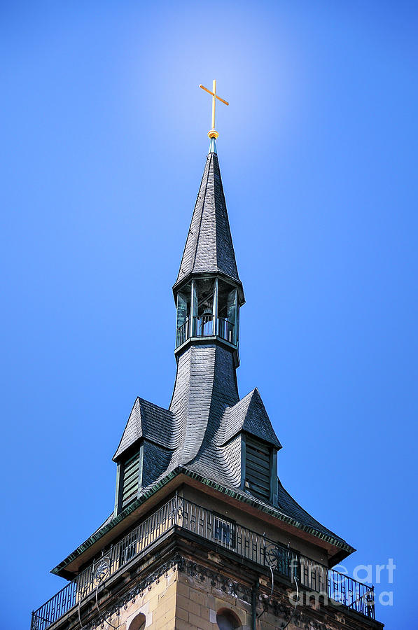Bright golden Cross on an ancient church spire shines high up in the royal blue sky. by Ulrich Wende