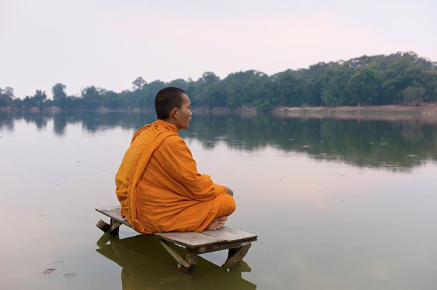 Buddhist Monk Sitting On Waters Edge Photograph by Martin Puddy