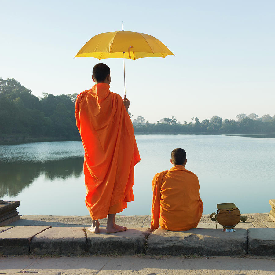 Buddhist Monks Standing In Front Of Photograph by Martin Puddy