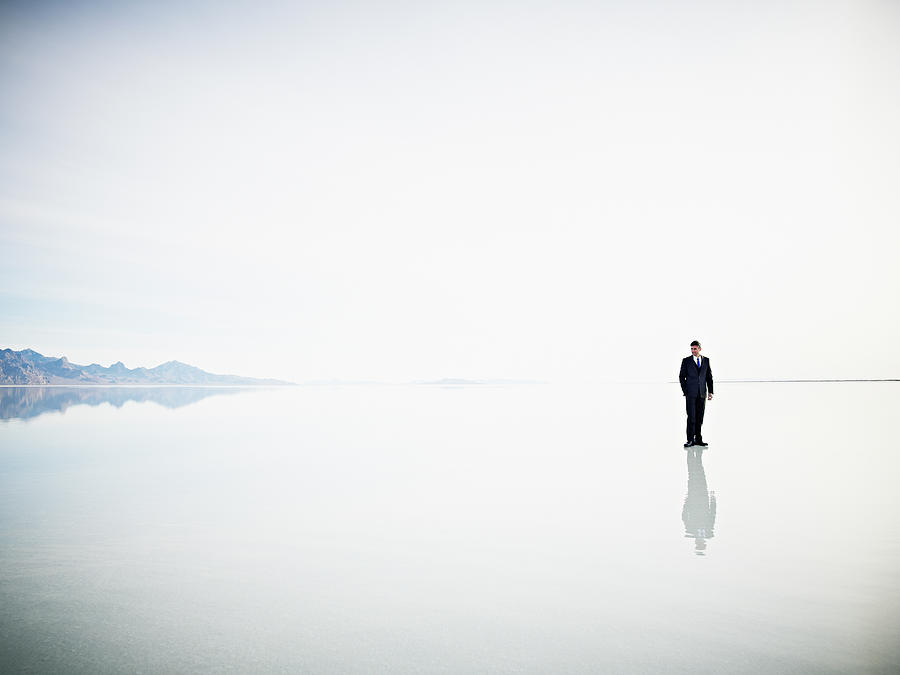 Businessman Standing Alone On Surface Photograph by Thomas Barwick