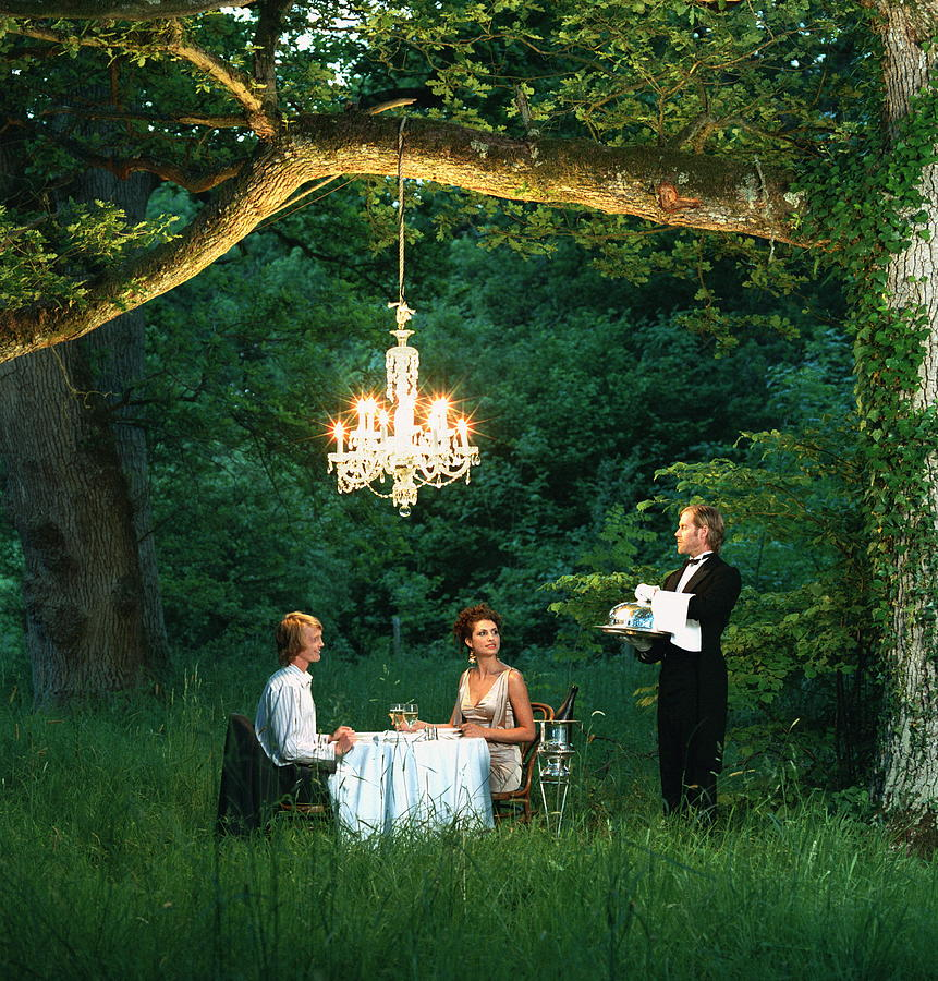 Butler Waiting On Young Couple Dining Photograph by Martin Barraud