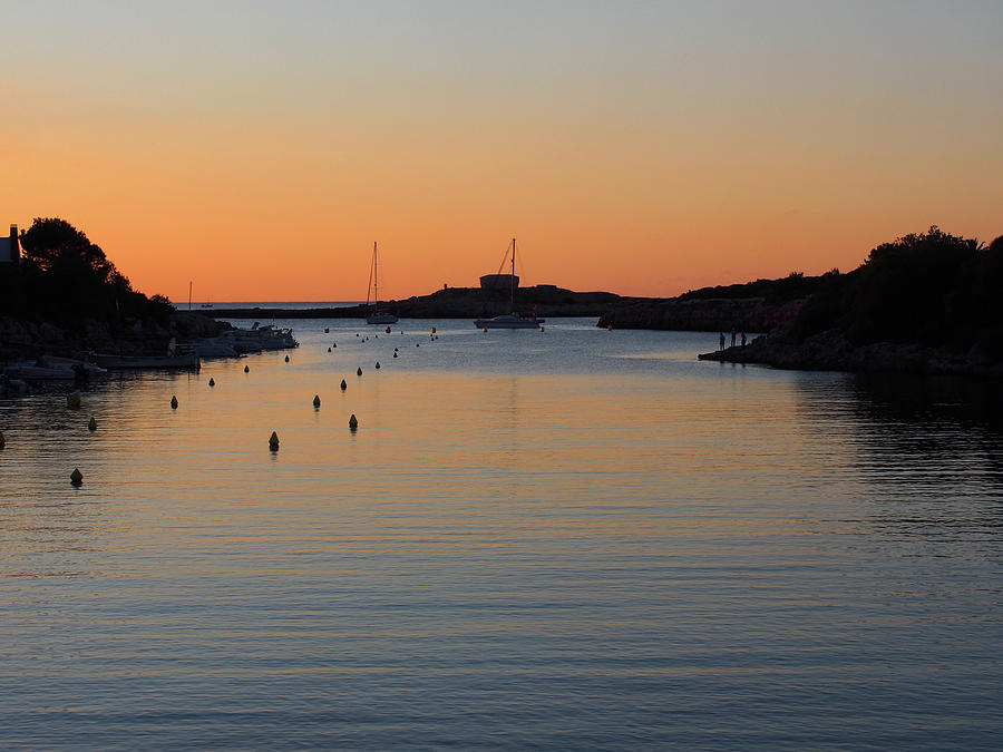 cala santandria in ciutadella at twilight with a glowing orange evening sky reflected in dark calm water of the bay with boats and coast in silhouette by Philip Openshaw