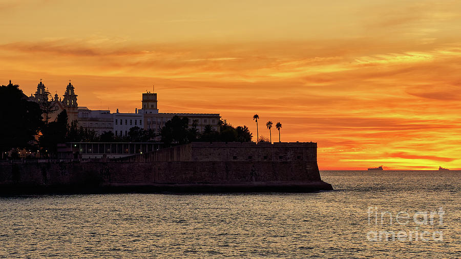 Candelaria Fortress Silhouette at Sunset against Orange Sky by Pablo Avanzini