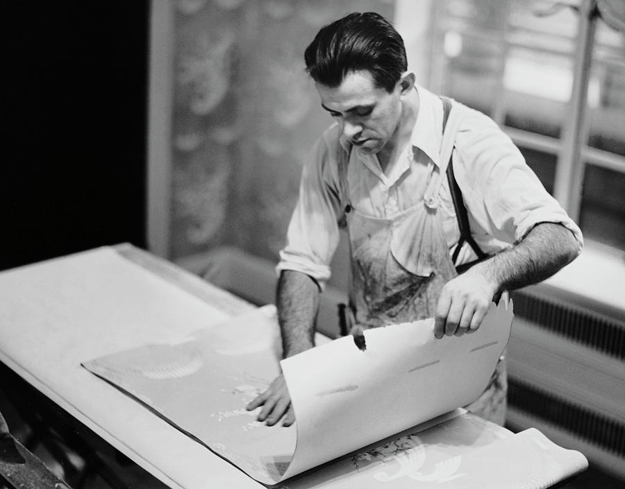 Carpenter Putting On Wallpaper Photograph by George Marks