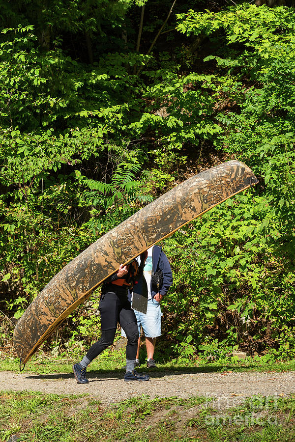 Carrying a camouflaged canoe by Les Palenik