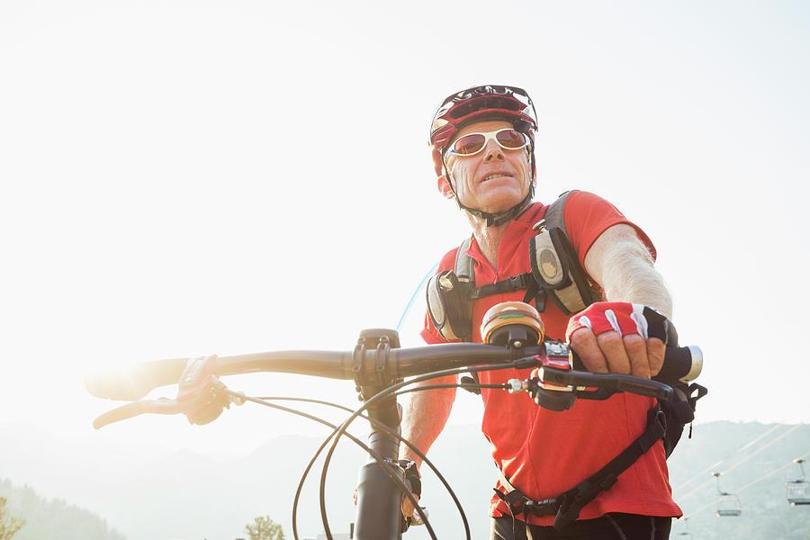 Caucasian Man Pushing Mountain Bike Photograph by Mike Kemp