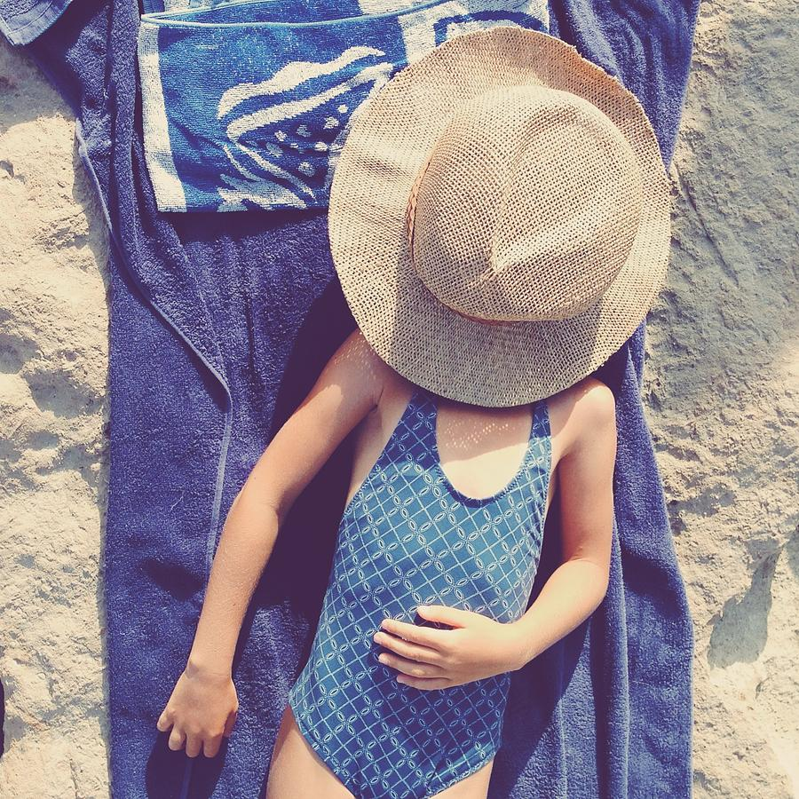 Child In Swimsuit Laying On Towel With Photograph by Jodie Griggs