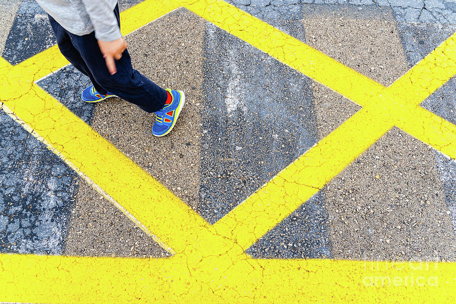 Child's legs on yellow lines on asphalt. by Joaquin Corbalan