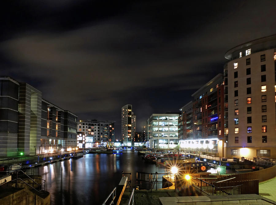 Clarence dock leeds at night with moored barges and moonlit clouds over brightly illuminated waterside buildings reflected in the harbour by Philip Openshaw