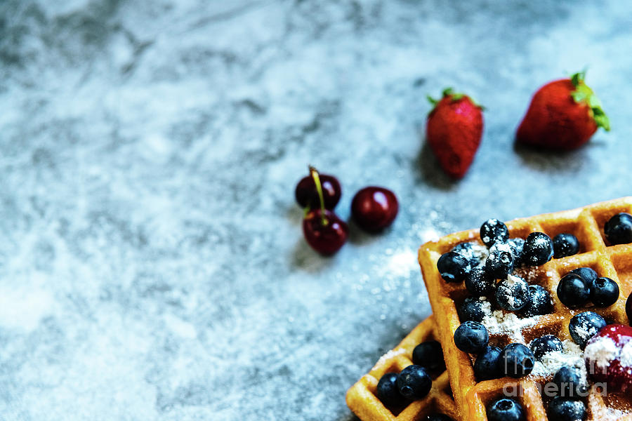 Clean background with negative space for healthy food and antioxidant fruits, and a waffle as junk food. by Joaquin Corbalan