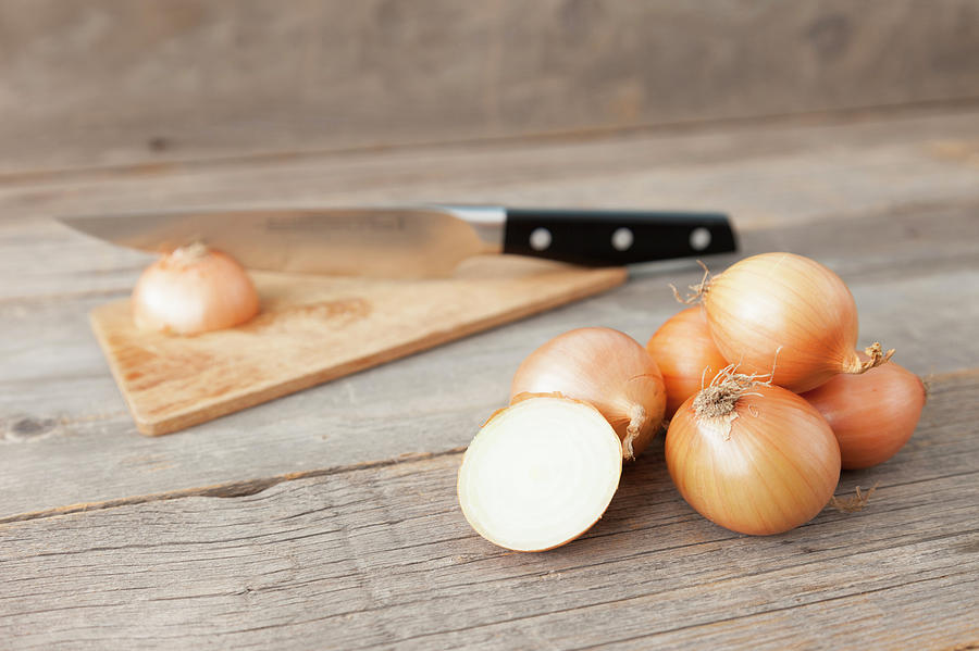 Close Up Of Onions And Knife On Table Photograph by Stefanie Grewel