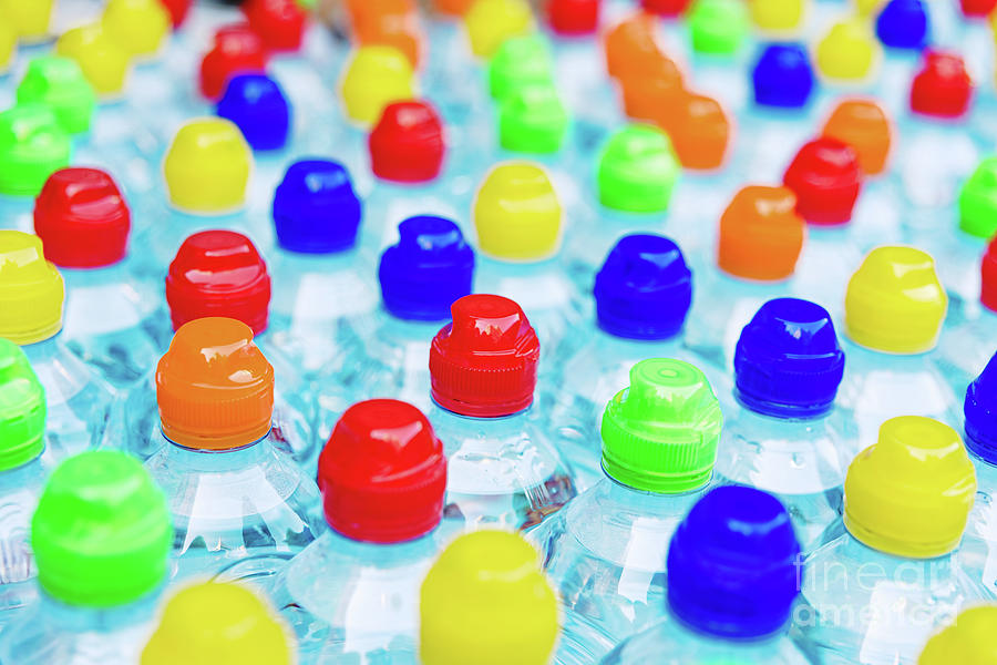 Colored stoppers of new plastic bottles, concept of pollution by recyclable plastics. by Joaquin Corbalan