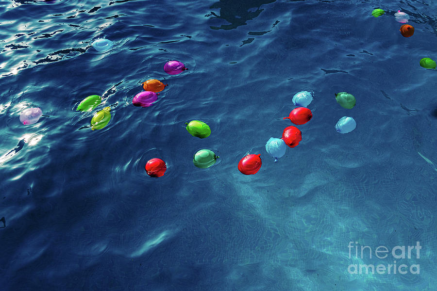 Colorful plastic water balloons floating in a pool to play on vacation to cool off. by Joaquin Corbalan