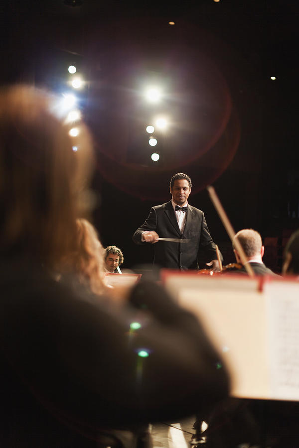 Conductor Waving Baton Over Orchestra Photograph by Hybrid Images