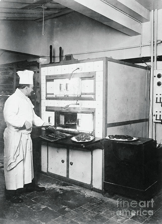 Cook Placing Pastries In Oven Photograph by Bettmann