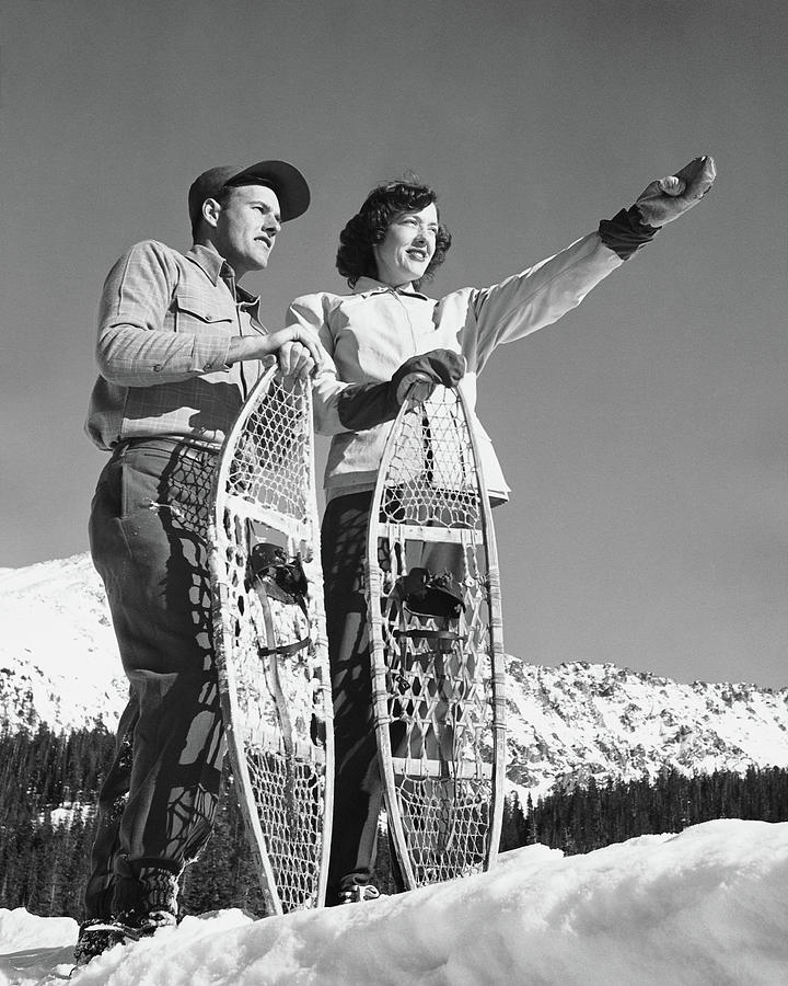 Couple Holding Snowshoes, Woman Pointing Photograph by Stockbyte