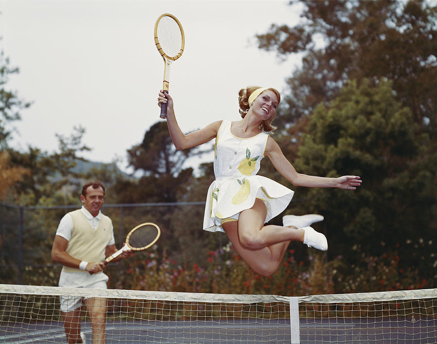 Couple On Tennis Court, Woman Jumping Photograph by Tom Kelley Archive