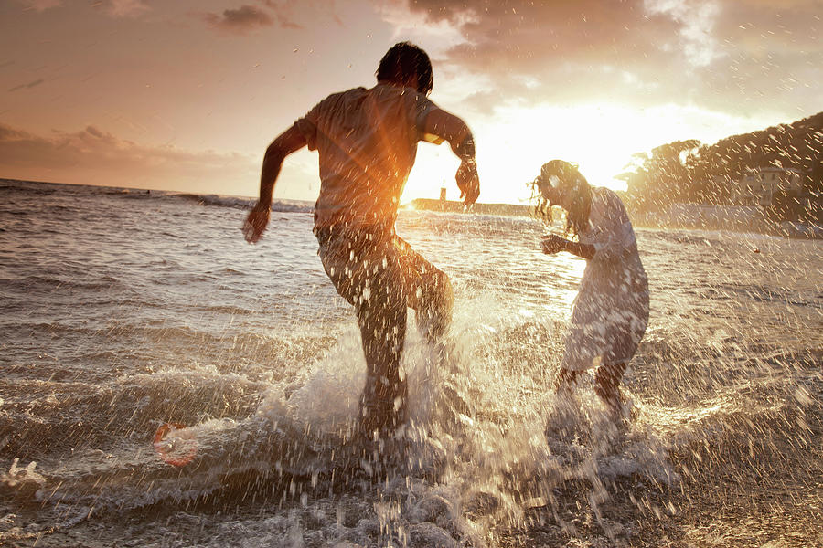 Couple Playing In Waves At Beach Photograph by Walter Zerla
