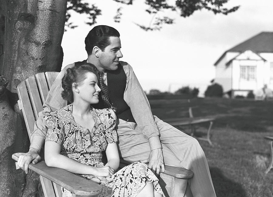 Couple Relaxing On Deckchair In Garden Photograph by George Marks
