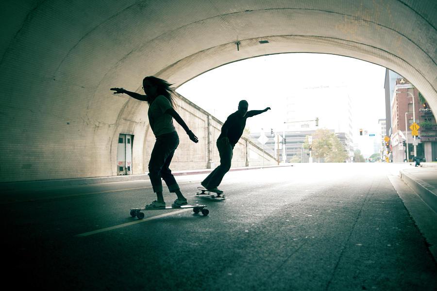 Couple Skateboarding Through Tunnel Photograph by Ian Logan