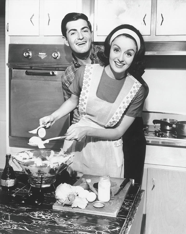 Couple Standing In Kitchen, Smiling, B&w Photograph by George Marks