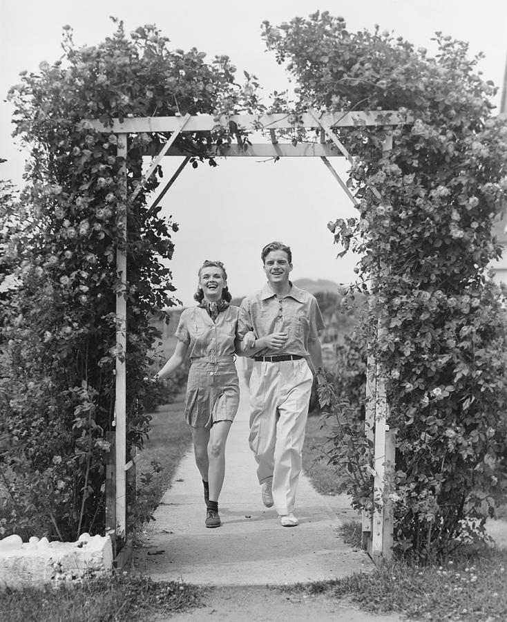 Couple Walking On Footpath Towards Rose Photograph by George Marks