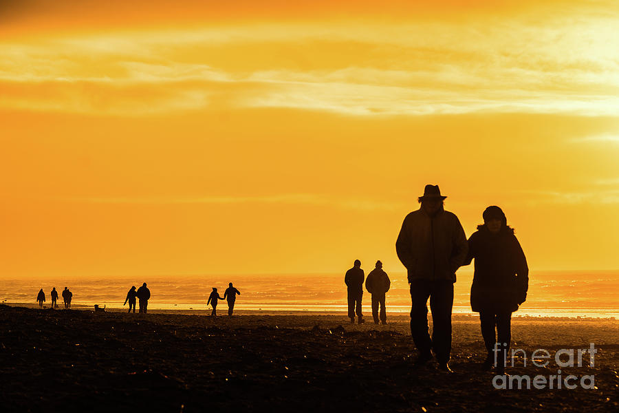 Couples Photograph - Couples Walking Along The Beach At Sunset by Keith Morris