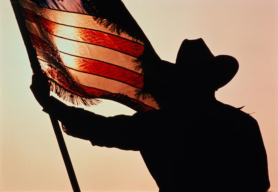 Cowboy Holding Stars And Stripes Photograph by Donovan Reese