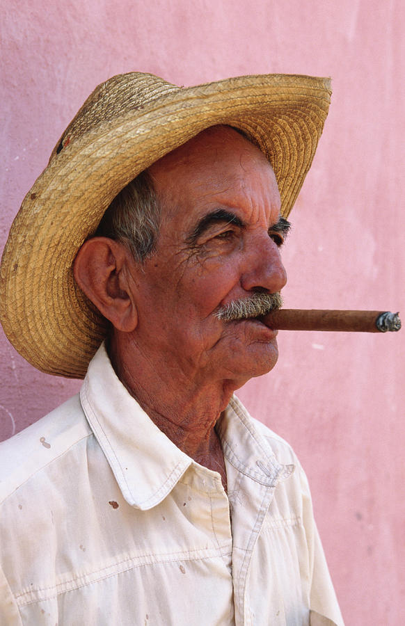 Cuban Man Smoking A Cigar Next To Pink Photograph by Tim Hughes