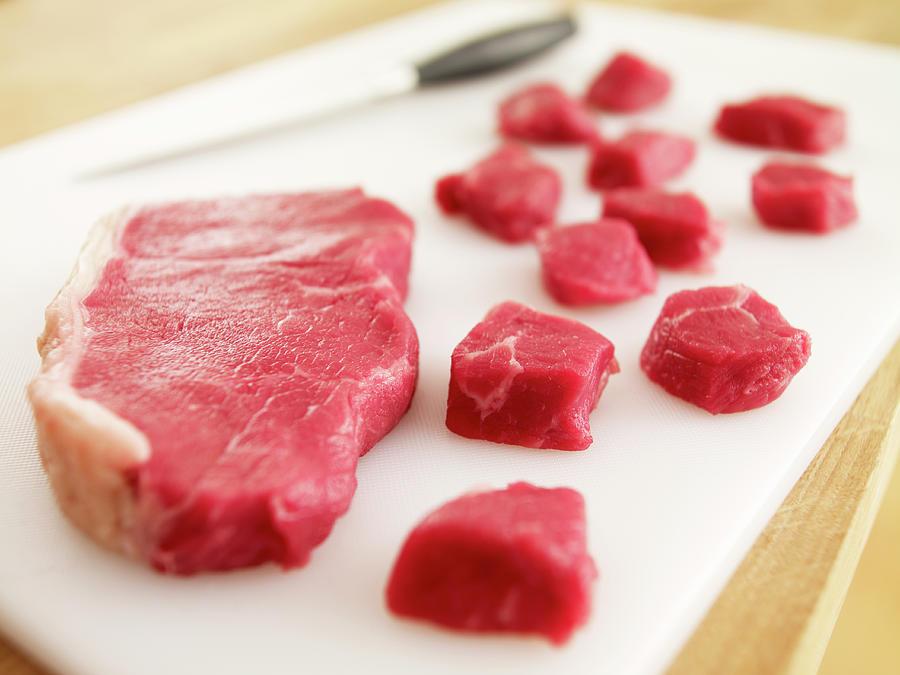 Cubed Raw Steak On Cutting Board Photograph by Adam Gault