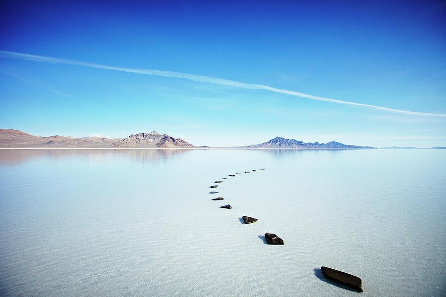 Curved Path Of Stones In Calm Lake Photograph by Thomas Barwick