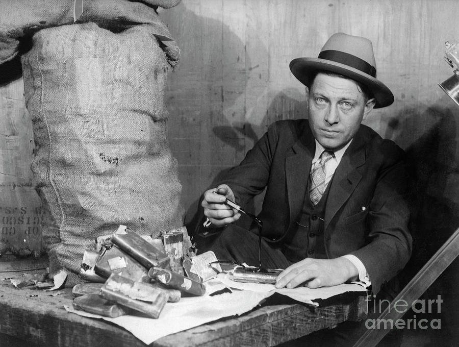 Customs Officer Examining Confiscated Photograph by Bettmann