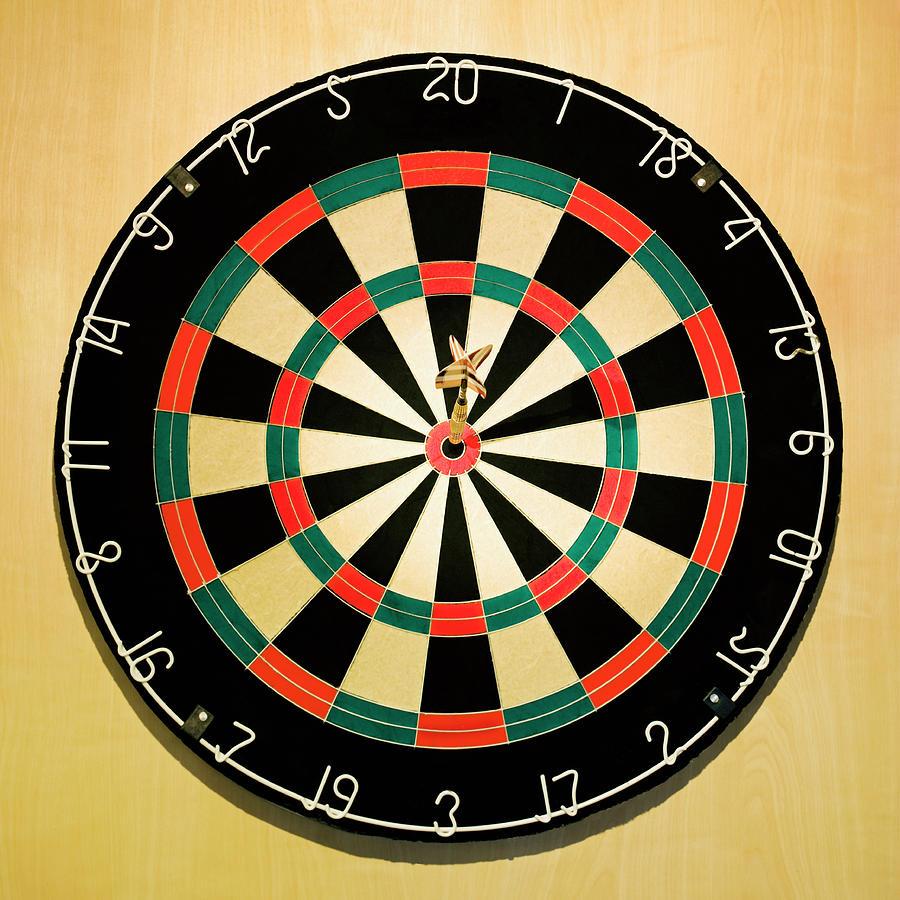 Dart In Bulls Eye On Dart Board Photograph by Fuse