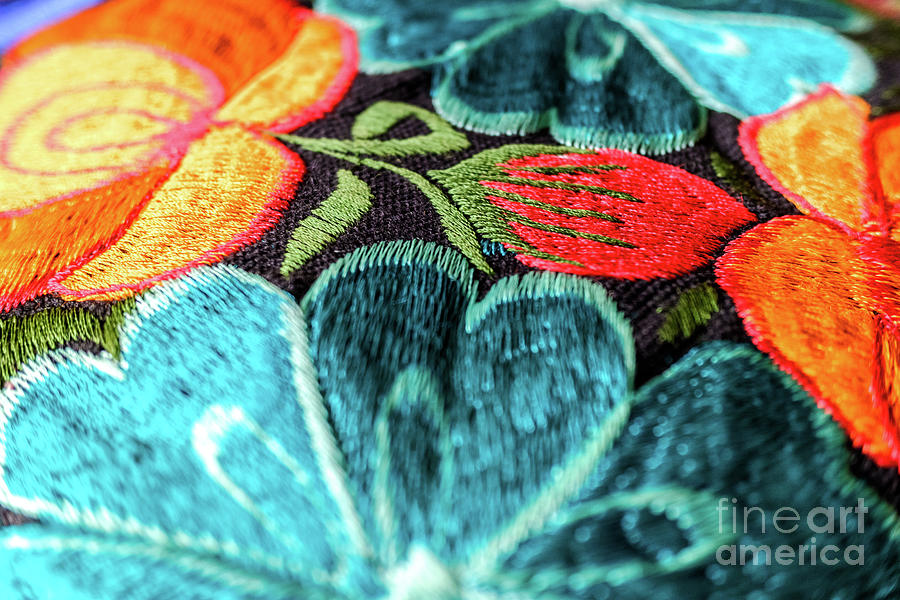 Detail of a colorful embroidery with flower motifs in brightly colored fabrics. by Joaquin Corbalan