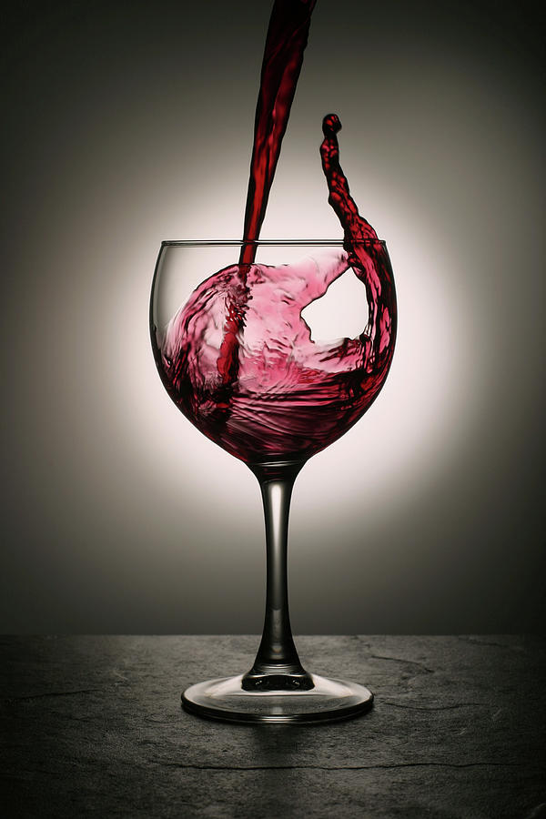 Dramatic Red Wine Splash Into Wine Glass Photograph by Donald gruener