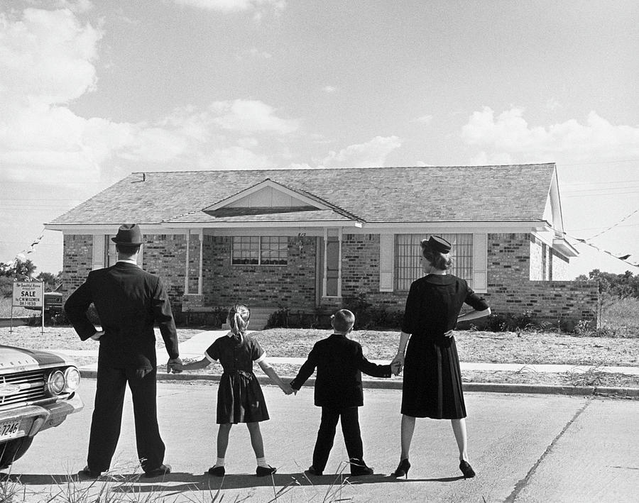 Family Holding Hands, Looking At A Photograph by Archive Holdings Inc.