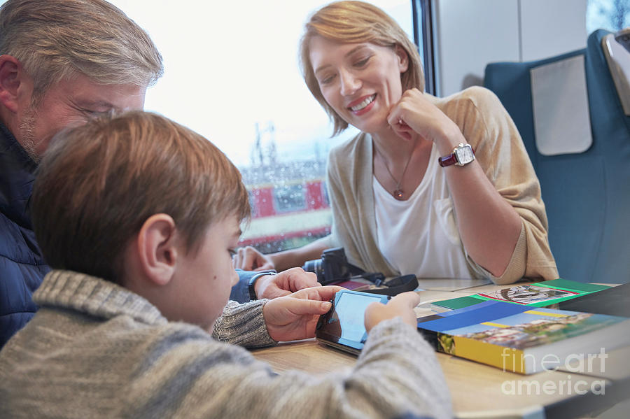 Boy Photograph - Family Using Smart Phone On Train by Caia Image/science Photo Library