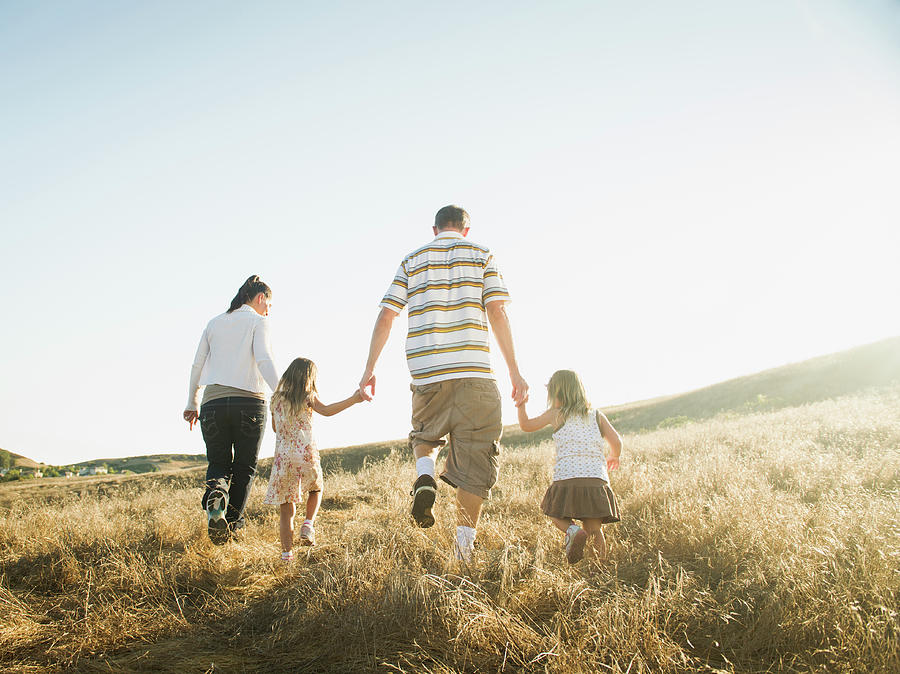 Family Walking Together In Rural Field Photograph by Erik Isakson