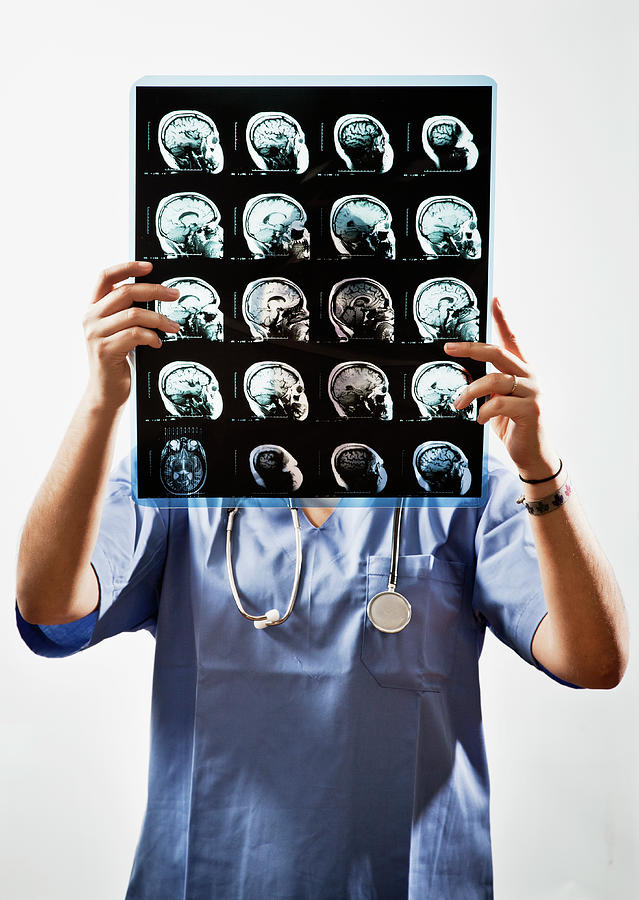 Female Doctor Holds Up Mri In Front Of Photograph by Ron Levine