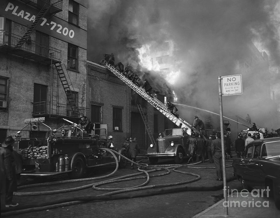 Firemen On Truck Ladder @ Burning Bldg Photograph by Bettmann