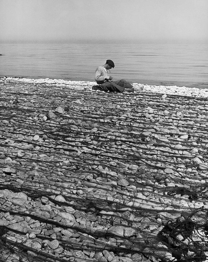 Fisherman Inspecting And Mending Nets Photograph by Alfred Eisenstaedt