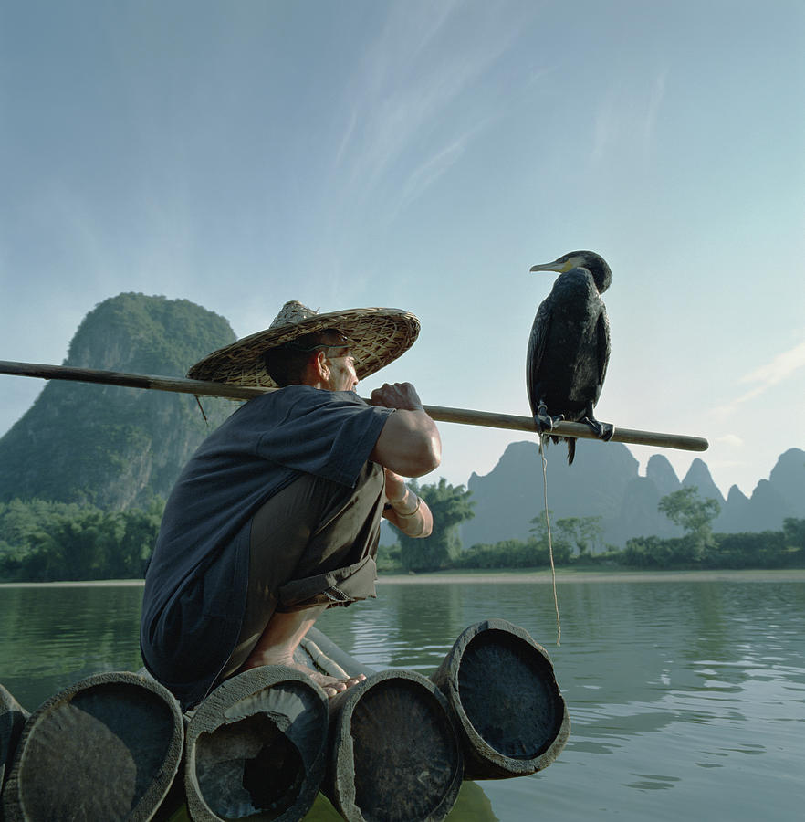 Fisherman Sitting On Bamboo Raft With Photograph by Martin Puddy