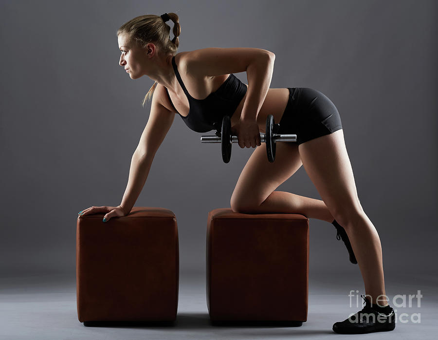 Fitness girl doing dumbbell rows by Catalin Petolea