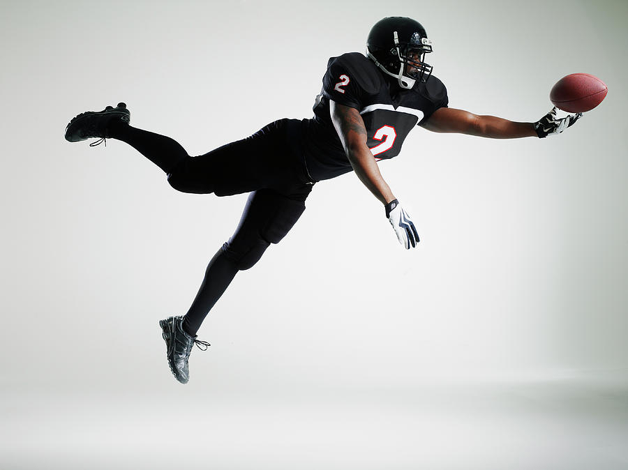 Football Player Leaping In Mid Air To Photograph by Thomas Barwick