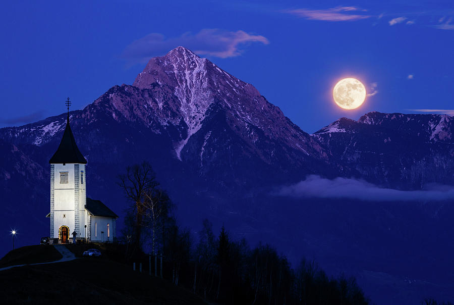Full moon rising over Jamnik church and Storzic at dusk. by Ian Middleton