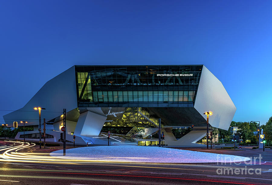 Futuristic architecture  of the Porsche Museum under a dark blue sky at dusk by Ulrich Wende