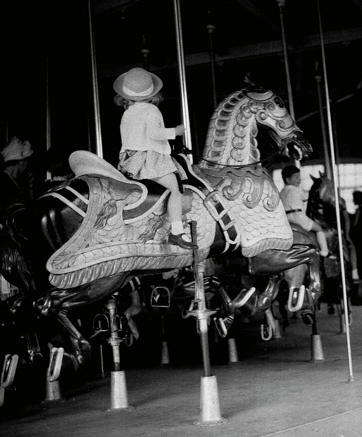 Girl Riding A Carousel Photograph by George Marks
