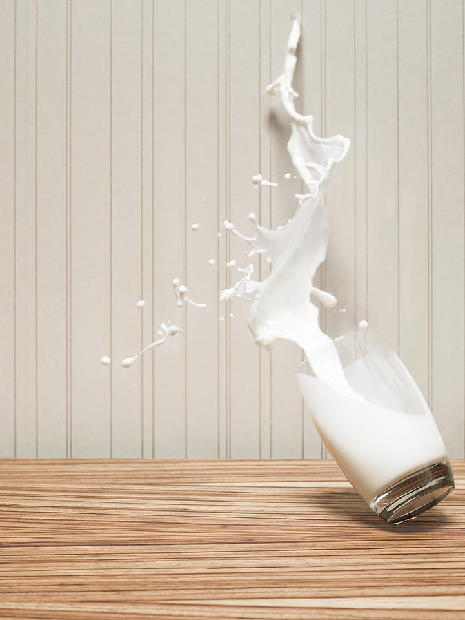 Glas Of Milk Spilling Photograph by Henrik Sorensen