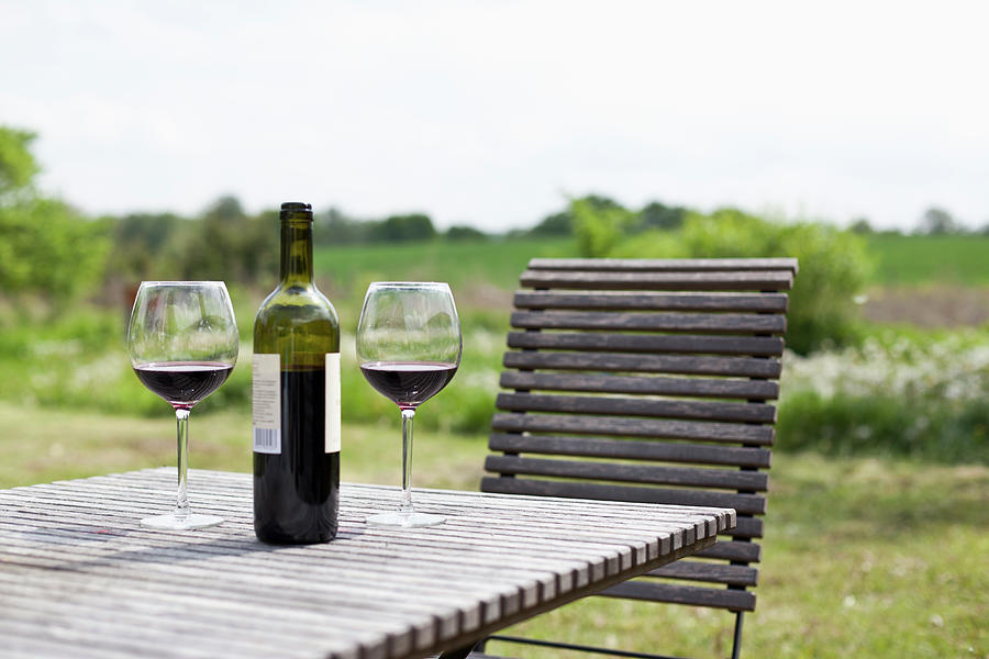 Glasses And A Bottle Of Red Wine On An Photograph by Halfdark