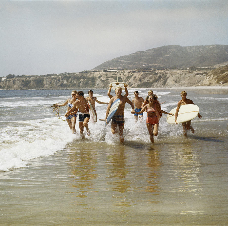 Group Of Surfers Running In Water With Photograph by Tom Kelley Archive